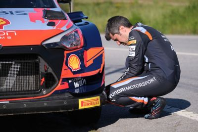 Hyundai Motorsport co-driver Borja Rozada kneeling next to the i20 Coupe WRC's front tyre.