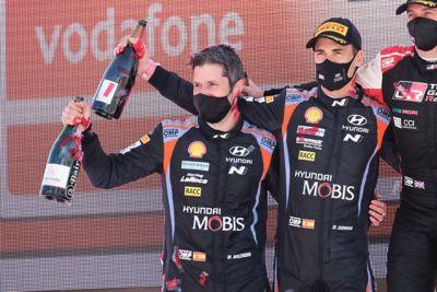 Hyundai Motorsport driver Dani Sardo and co-driver Borja Rozada celebrating with champagne.