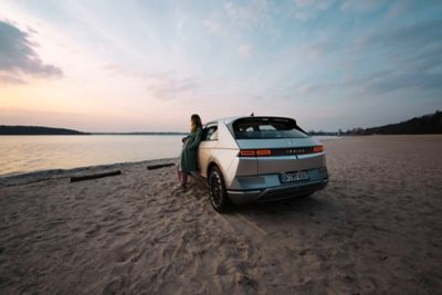 The Hyundai IONIQ 5 electricmidsize CUVparked at the beach with a woman leaning against it, enjoying the sundown.