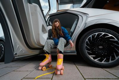 A woman wearing pink rollerskates sitting in the rear door of the Hyundai IONIQ 5 electric midsize CUV.