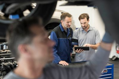 Servicemenn sjekker en Hyundai elbil. Foto.