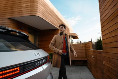 A man in brown coat walking around the Hyundai IONIQ 5 electric midsize CUV.