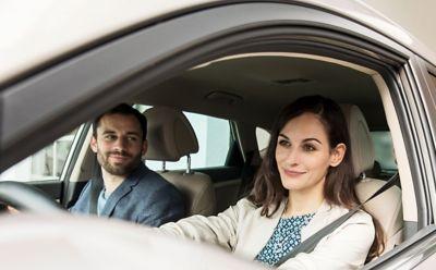 Kobieta i mężczyzna siedzą w samochodzie, rozmawiają o programie Hyundai Promise.