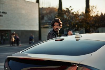 Imagen del nuevo Hyundai IONIQ Híbrido con un hombre junto a él.