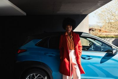 A woman in a long red coat, leaning against the passenger door of her Hyundai KONA Hybrid.