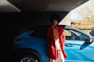 Woman leaning against a Hyundai Kona Hybrid.