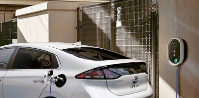 Hyundai IONIQ plugged into a wallbox on an outside wall