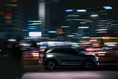 Hyundai-modell kjører i opplyst by om natten. Foto.