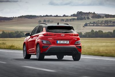 The Hyundai Kona N Line driving in the countryside from the rear.