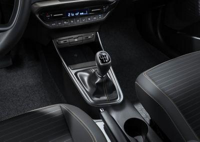 Una palanca de cambios de transmisión manual dentro de un nuevo Hyundai i20, vista del lado del pasajero