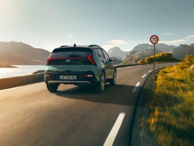 De Hyundai BAYON, de nieuwe, compacte crossover-SUV op de weg, van achter gezien.