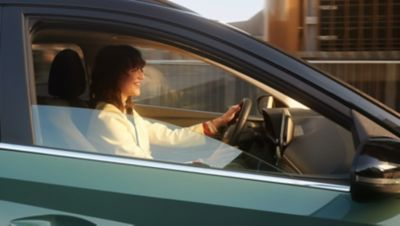 Vrouw bestuurt de Hyundai BAYON, de nieuwe, compacte crossover-SUV, gezien door de zijruit rechtsvoor.