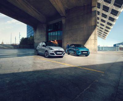 Dwoje kierowców stojących przy swoich sportowych Hyundaiach i10 Nowej Generacji