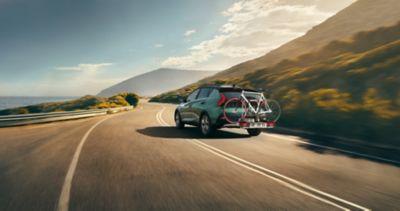 Hyundai BAYON con barra de remolque y portabicicletas circulando por una carretera rural.