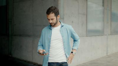 Un uomo che guarda lo smartphone per la ricarica programmabile di Nuova Hyundai Kona Electric.