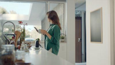 Imagen de una mujer en una cocina, con una taza en la mano y su smartphone en la otra, y un Hyundai aparcado en la entrada.