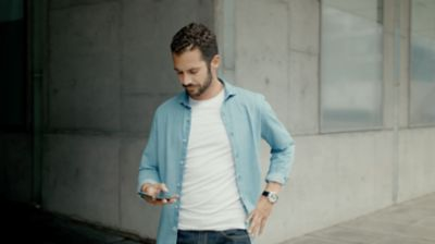 A man looking at his smartphone for the programmable charging of the new Hyundai Kona Electric.