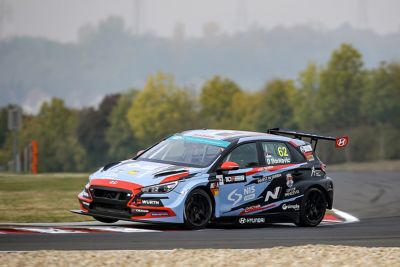 The Hyundai Motorsport's i30 VELOSTER N TCR in action on a racetrack shown from the side.