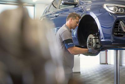 Tekniker sjekker bremser under service. Foto.
