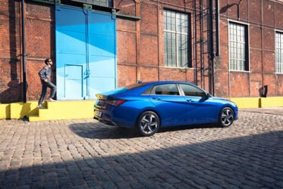 Nowy Hyundai Elantra pokazany z boku zaparkowany przed magazynem.