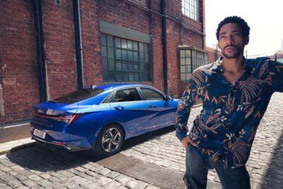 Nowy Hyundai Elantra pokazany z tyłu i mężczyzna stojący na pierwszym planie.