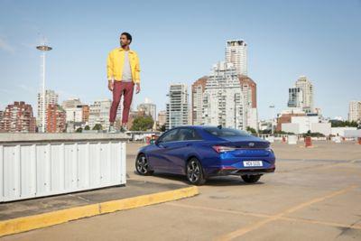 Nowy Hyundai Elantra pokazany z tyłu i mężczyzna stojący obok niego.