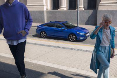 Nowy Hyundai Elantra pokazany z boku, zaparkowany w mieście i oddalający się od niego ludzie.