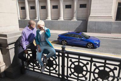 Nowy Hyundai Elantra pokazany z boku zaparkowany w mieście i dwóch ludzi siedzących przed nim.