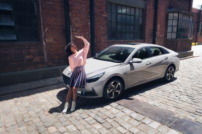 Nowy Hyundai Elantra na ulicy ukazany z przodu i opierająca się o niego dziewczyna.