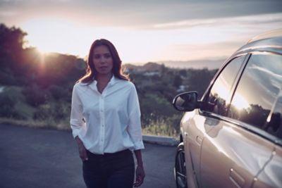 Dame ved siden av en Hyundai NEXO. Foto.