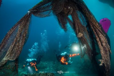 Two divers from Ghost Divers recovering discarded fish nets underwater for recycling.