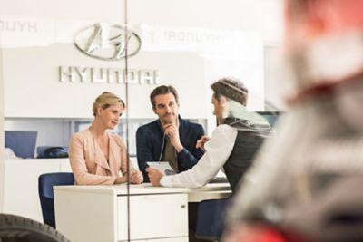 Kobieta i mężczyzna słuchający o programie Hyundai Promise.