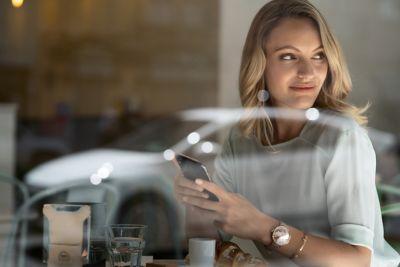 Dame på cafe med telefon. Foto