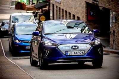 Hyundai IONIQ Electric i front av en rekke kjørende elbiler. Foto.