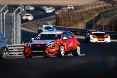 A picture of Hyundai Motorsport's i30 N TCR in action on a racetrack shown from the front.