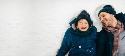 Far og sønn leker i snøen. Foto.