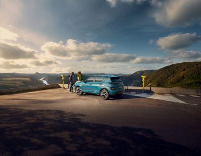 Nouveau Hyundai KONA Electric stationné sur un parking avec vue panoramique sur la campagne.