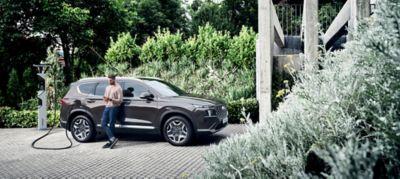 Homme et femme appuyés contre le Nouveau Hyundai SANTA FE Plug-in.