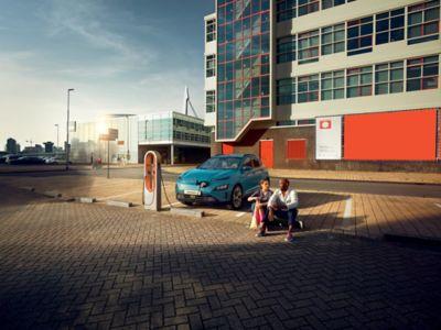 Couple assis près du nouveau Hyundai KONA Electric en cours de recharge sur une borne publique.
