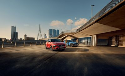 Deux nouveaux SUV Hyundai KONA N Line stationnés sous un pont.