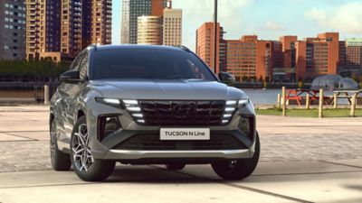 Frontview of the all-new Hyundai TUCSON Plug-in Hybrid N Line in shadow gray in front of a skyline.