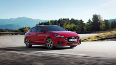 The new Hyundai i30 N racing a corner in the colourEngine Red.