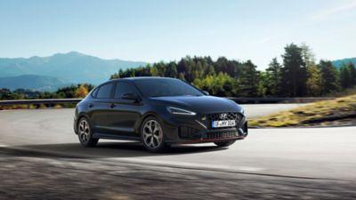 The new Hyundai i30 N racing a corner in the colour Phantom Black Pearl.