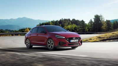 The new Hyundai i30 N racing a corner in the colour Sunset Red.