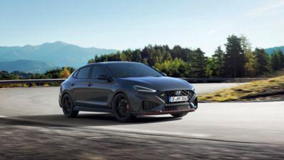 The new Hyundai i30 N racing a corner in the colour Dark Knight Pearl.