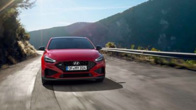 The new Hyundai i30 N driving in a hilly set in the colour Engine Red.