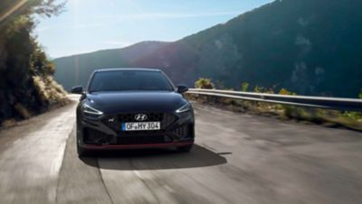 The new Hyundai i30 N driving in a hilly set in the colour Phantom Black Pearl.