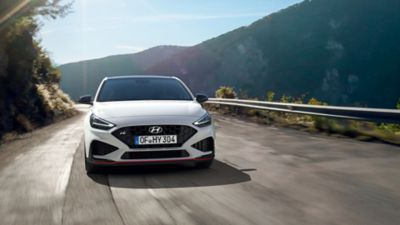 The new Hyundai i30 N driving in a hilly set in the colour Polar White.