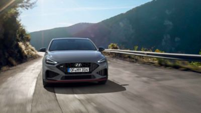 The new Hyundai i30 N driving in a hilly set in the colour Shadow Grey.