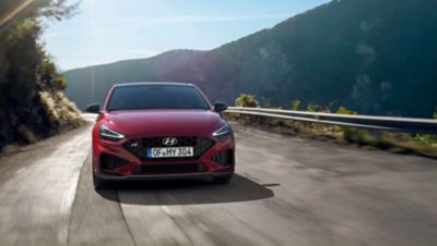 The new Hyundai i30 N driving in a hilly set in the colour Sunset Red.